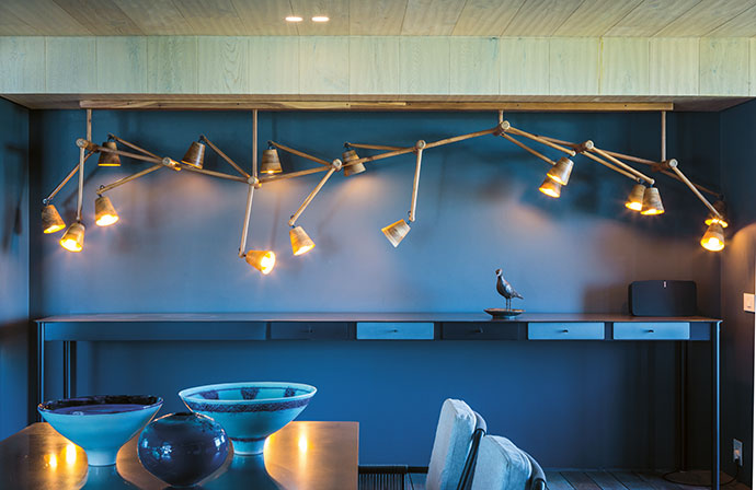 In the informal dining area, David Krynauw's Haywire chandelier hangs above a custom-made 4 m-long table with drawers by Gregor Jenkin Studio, which also made the telescopic extendable dining table on wheels.