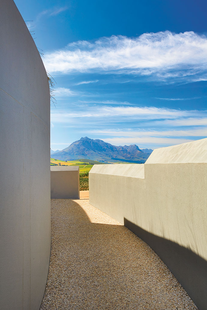 The curved walls mirror the Cape Fold Mountains in the distance, and the exposed aggregate concrete paving has a rustic, natural look.