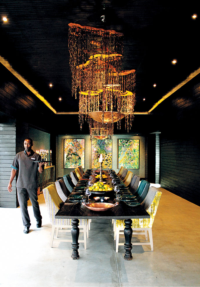 "Butler Xolisa Khatu walks past the ironwood dining table, which is laid for a feast. The delicate chandelier by Gregg Brill features more than 1 km of antique copper chain and ""leaves"" of copper and coconut husk chips. The artworks against the back wall are by Anastasia Pather, who was commissioned to depict the Rain Queen Modjadji, and The Grand Living was commissioned to make the bronzed-metal Twig server."