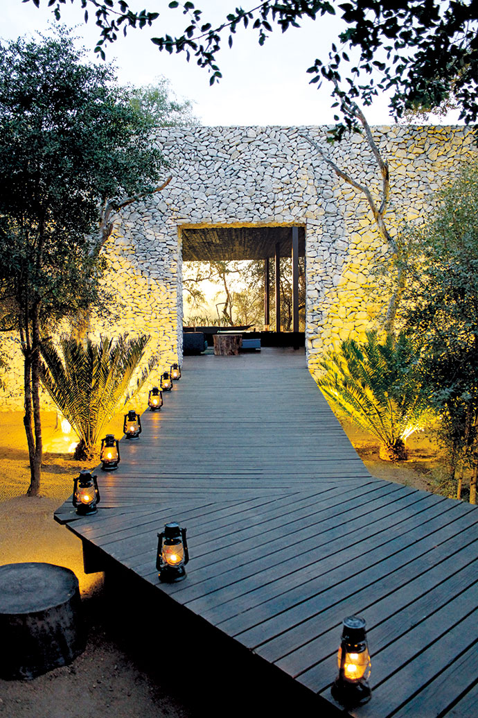 "A boardwalk winds through a fever-tree forest and then past leadwood trees and cycads to an unobtrusive opening in the great granite ""spine"", the wall that forms the backbone of the lodge."