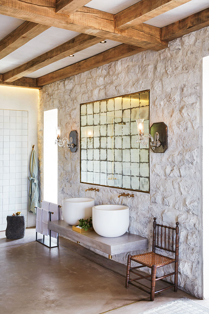 The guest villa bathrooms feature custom-made sanitaryware. The generous basins appear weightless on the floating concrete base, and the Perrin & Rowe taps have a raw brass finish. The 18th-century tolletjie chair is from Pier Rabe Antiques.