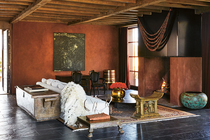 The main living room features a rare Persian carpet, an antique Indian kist, a sofa custom-made in antique linen, artwork by Peter Eastman, and a pair of Smoke armchairs from Moooi. The metal-clad fireplace is adorned with an oversized amber necklace. The ceiling is solid French oak with beams by Pierre Cronje.