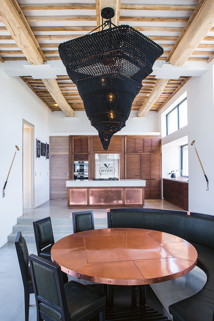 The kitchen features American walnut and copper, and a chandelier by Ashlee Lloyd. The dining table by Herman Brink Wooden Furniture picks up on the copper theme.