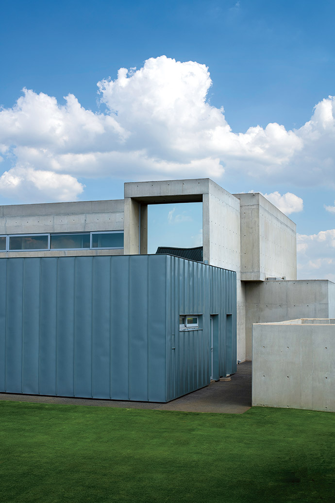Dominique clad the utility box in Rheinzink. Alongside it, behind concrete walls, the VRV air-conditioning system, back-up generator and heat pumps all aid the house in running with a low energy output. The main bathroom with its large one-way-glass window protrudes from the plane of the top floor.