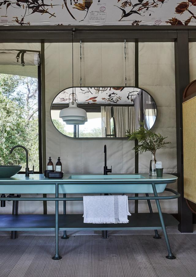 The vanity and mirrors, designed by SRLC Architects, were inspired by old enamel wash bowls and wash stands. The vanity top was cast by Boutique Baths.