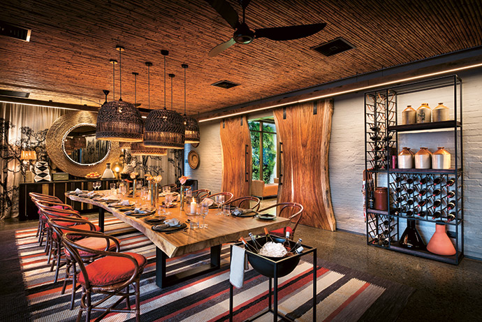 The hero of the elegant dining room is the custom-made beaded mirror from Sithabe African Craft in Cape Town. A cluster of oversized Ghanaian basket-weave pendants above the 12-seater dining table create intimacy. The striped woollen carpet is from Shuttleworth Weaving in the KwaZulu-Natal Midlands.