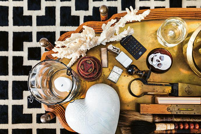"The collection of curiosities on the coffee table includes a Damian Hirst skull, a gift from interior designer Julia Day; shears from a garden shop in Paris; and red round boxes, mementoes from ""an unforgettable holiday in Lamu""."