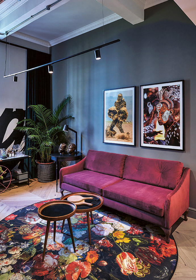 A bedroom-suite lounge features a Moooi carpet, photographic art from Carol Beckwith and Angela Fisher's African Twilight series from THK Gallery, a David Brits mural and a drinks trolley by Douglas & Company.
