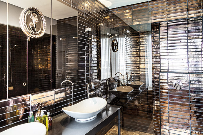 Warm metallics add an edge of contemporary opulence throughout the apartment. The bronze tiles in this guest bathroom were made by Southern Art Ceramics, and the vanity is by Gregor Jenkin.