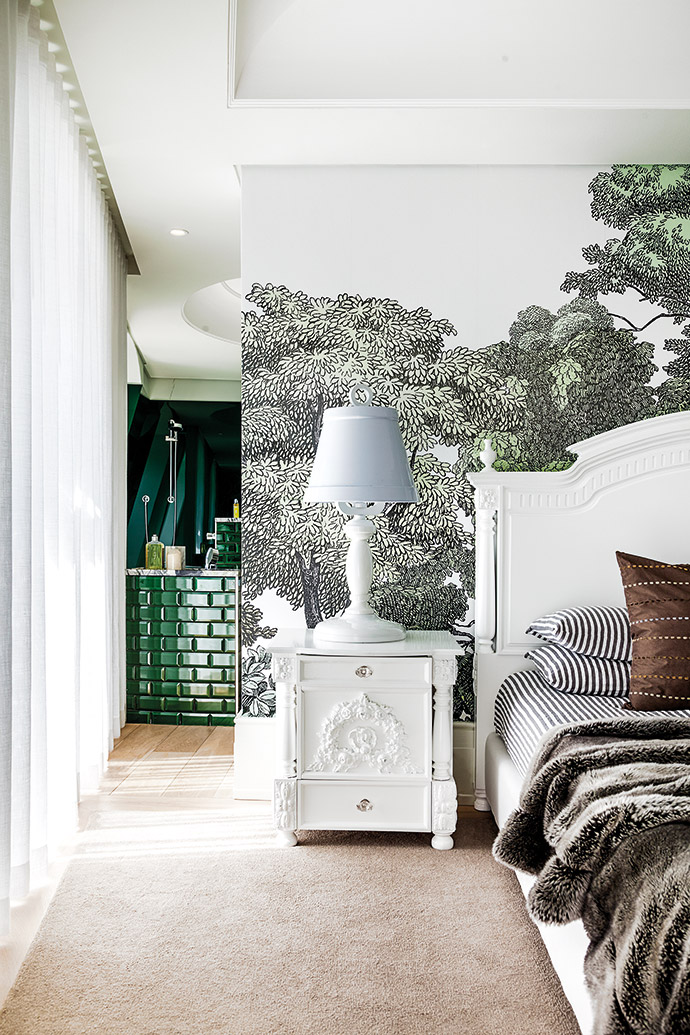 In this en-suite guest room, whimsical wallpaper (Rebel Walls Bellewood from St Leger & Viney), tiles in a punchy green (from Douglas Jones) and grey-and-green Monet marble (from WOMAG) echo the verdant shades of Green Point Urban Park, which the apartment overlooks. Both the replica table lamp and the replica LED pendant lamp are from Maxim Lighting, and the mirror is from Loft Living.