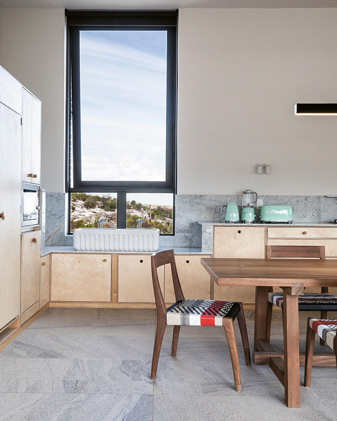 A large vertical window in the kitchen lets in plenty of light and offers a view of the sea in the far distance. A white hand-made sink by Shaws of Darwen and pastel-green Smeg appliances add a retro touch. The table is by James Mudge and the chairs are by Vogel Design.