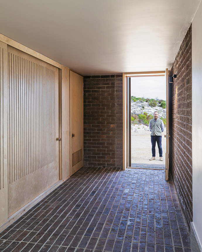 Architect Guillaume Pienaar standing at the front door, which leads into the brick entrance-cum-wet-room, which has ample cupboard space for storing the active family's hiking and running gear.