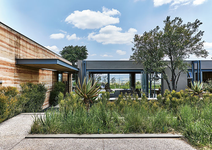 The rammed-earth wall runs from the entrance all the way through the house.