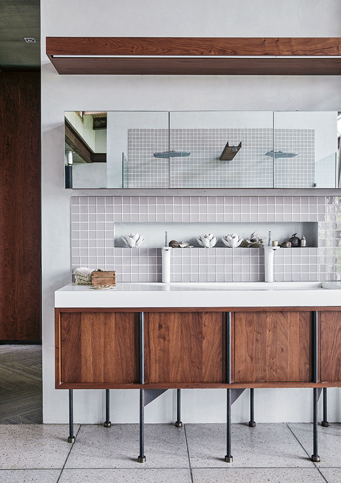 The main en-suite bathroom, between the bedroom and the dressing room, features a freestanding bath that is positioned so it affords views as well as privacy. The cool palette of glass tiles and pale terrazzo is refined and calming, whereas details such as the steel I-beams pick up on the industrial elements in the architecture of the house. Gillian designed and made the vanity.
