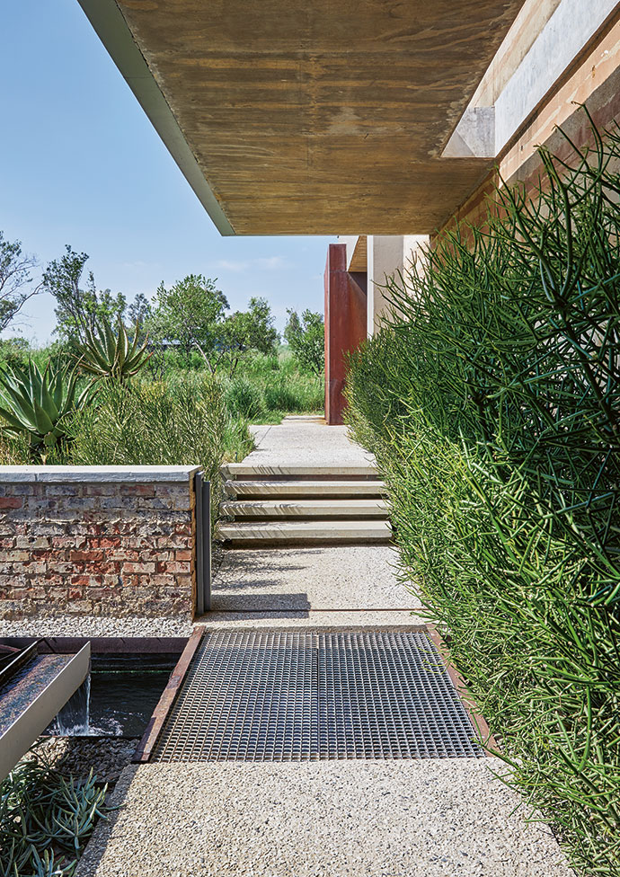 A cantilevered concrete canopy provides shelter as you approach the front door along a path and a bridge over a koi pond.