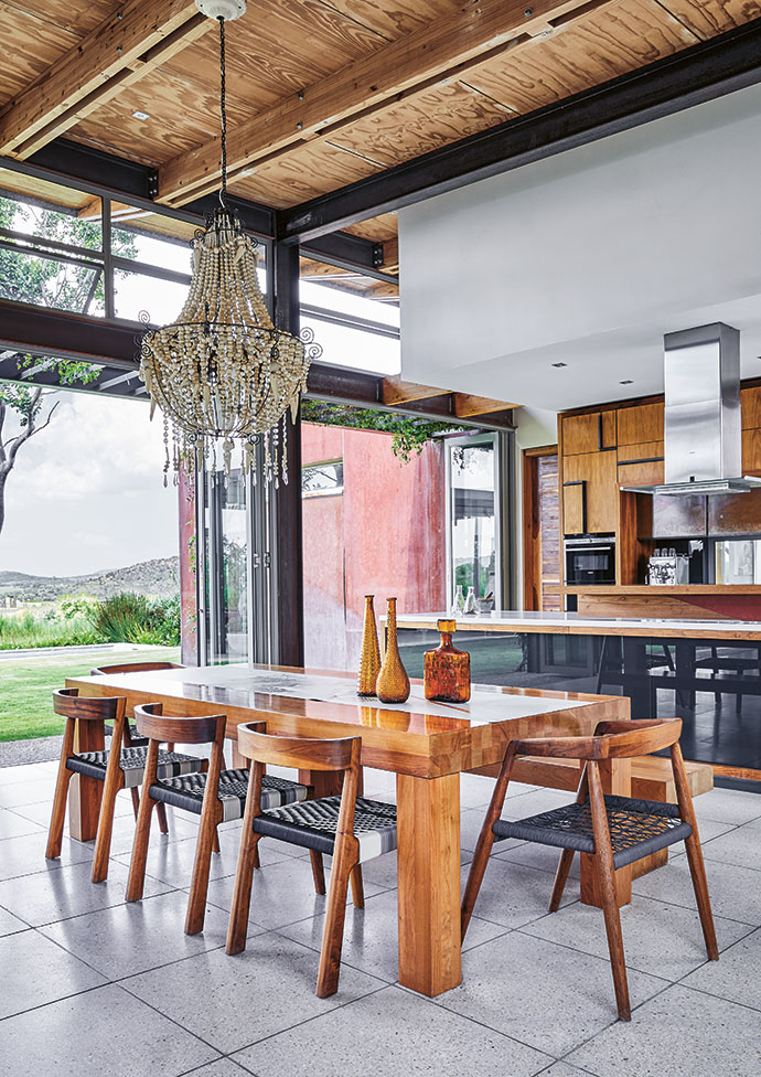 Gillian designed the teak kitchen cabinetry, with handles made out of recycled window frames, as well as the rosewood dining table. The tub chairs are by Vogel Design and the chandelier by Mud Studio.