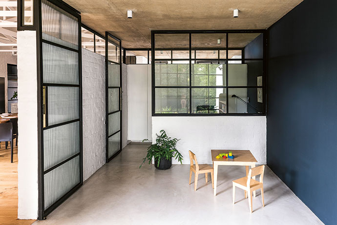 The study is separated from the children's playroom by a steel-and-glass panel to allow supervision. The kids' table and chairs are by Pedersen + Lennard.