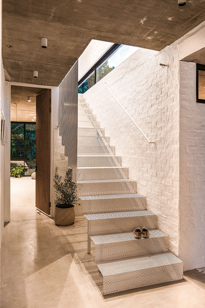 A perforated-steel staircase sits lightly in the passage and allows light to visually maximise an otherwise narrow space.