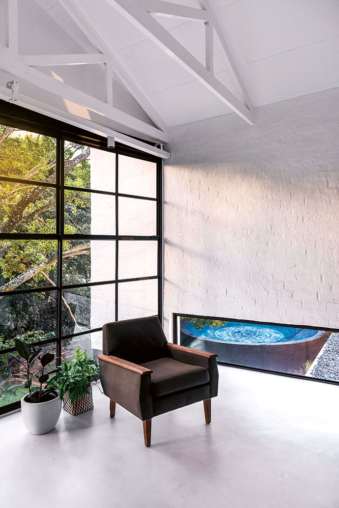An upstairs guest bedroom has a low strip window to offer a glimpse of the mosaic on the floor of the pool.