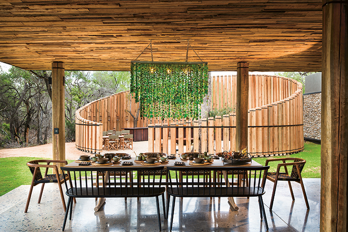 Breakfast and lunch are usually served family-style for guests to help themselves, at outdoor settings like this. The chandelier, made of recycled green glass, is by Ilovani; the dining table was custom-made by Egg Designs; the benches are by Houtlander; and the dining chairs are by Vogel Design.