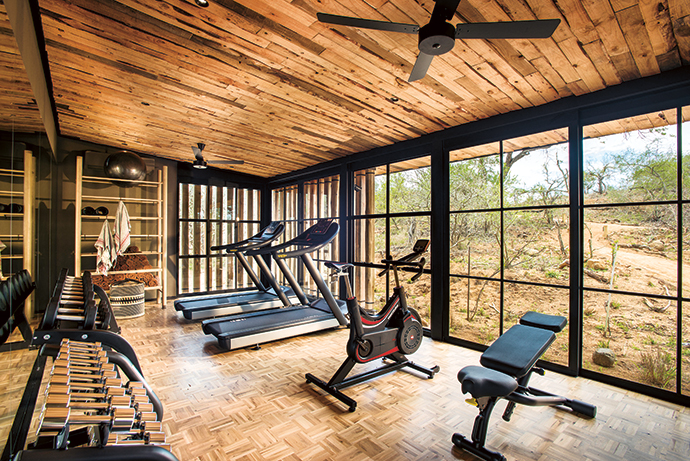 The boundary between inside and outdoors is blurred even in the gym, but air-conditioning provides welcome respite from the summer heat. Parquet hardwood flooring is used here and, as elsewhere, the ceiling is made of offcut timber from nearby sawmills.