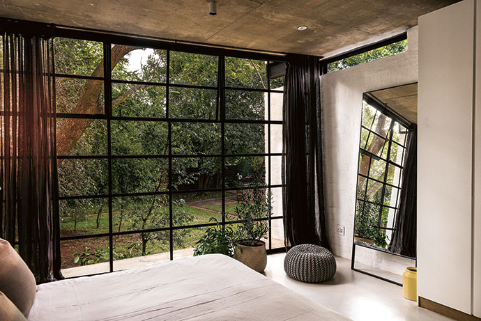 The new bedroom windows were designed to be at an angle skew to the walls so they face north. Strip windows allow continuous glimpses of the garden throughout the house.