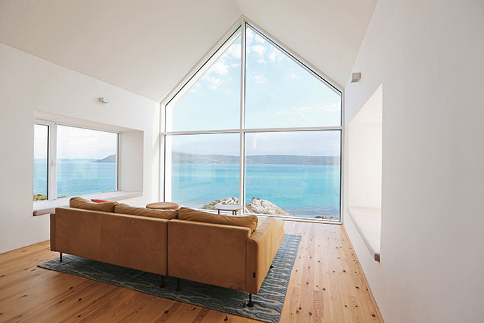 """Reading a novel – or three – in the lounge window nook while being warmed by the afternoon sun is a popular pastime for the Dalkmanns. The """"glass gable"""", a smart play on the Cape Dutch vernacular, affords uninterrupted views of the lagoon and allows sunlight to flood into the interior. The contemporary furnishings include a leather sofa from Weylandts, an occasional table by James Mudge and a rug from Gonsenhausers Fine Rugs."""