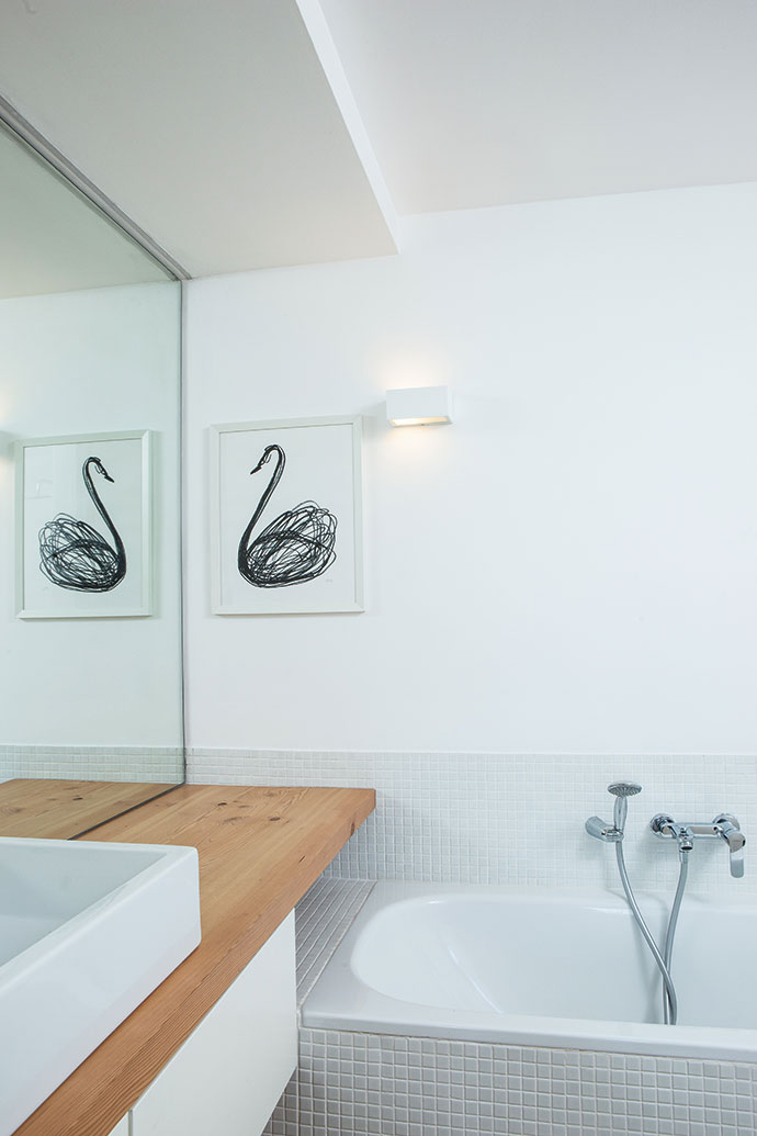 Well-considered joinery by Wolfgang Kretschmer throughout the house makes for seamless continuity. Freestanding basins, unframed mirrors, unobtrusive downlights and unassuming white mosaic tiles combine to create a low-key family bathroom.