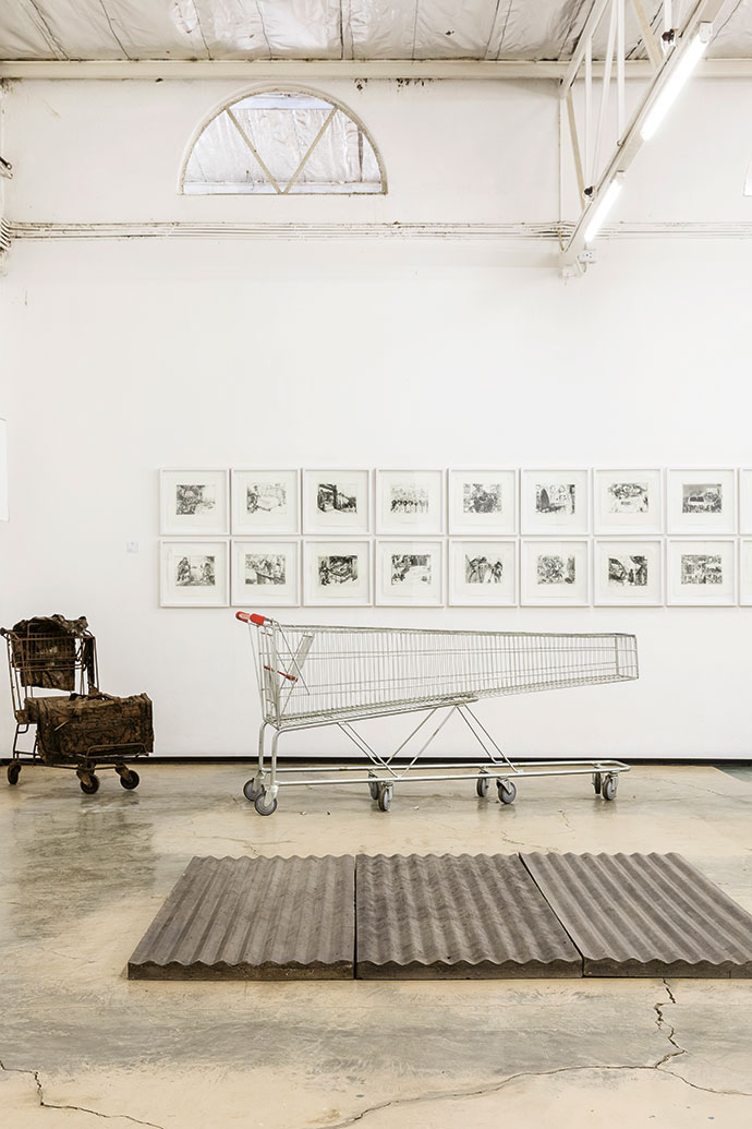 In the foreground, Corrugated Floor by Jeremy Wafer, 2014, three cast-concrete panels; Hyper Shopper by Jacques Coetzer, 2006, sculpted trolley; and, in the background, Disasters of Peace by Diane Victor, 2001 – 2011, etching on paper.