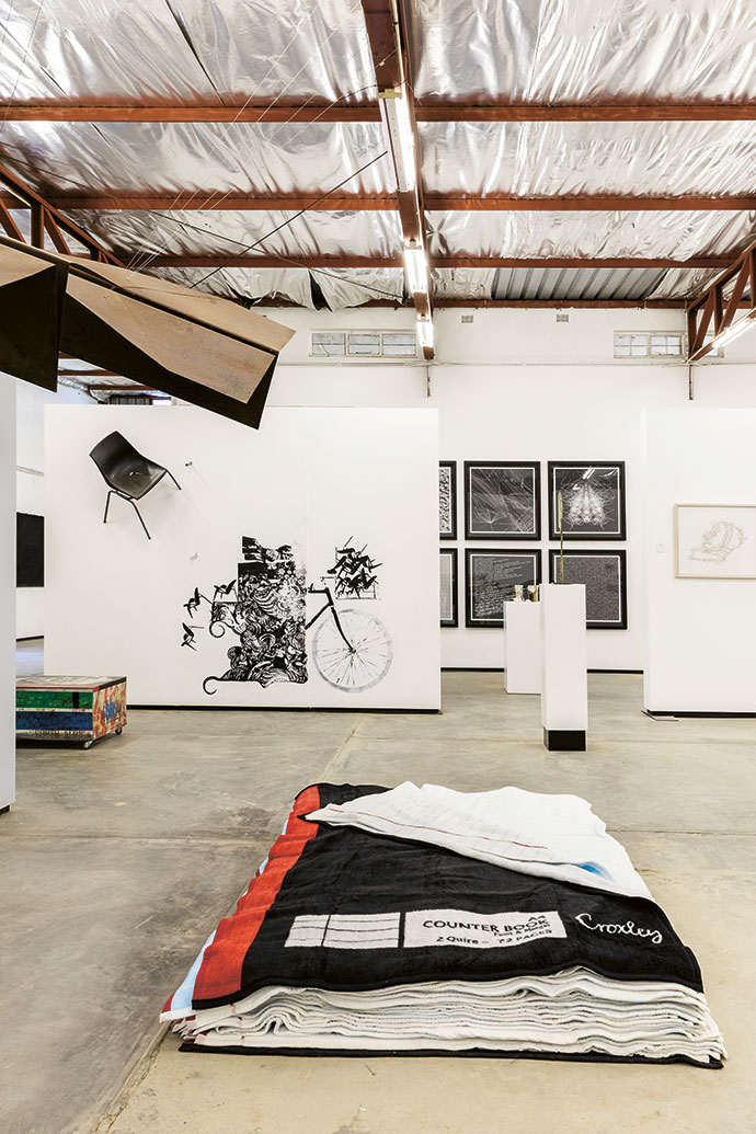 In the foreground is Pile: Feint and Margin by Maja Marx, 2010, 30 blankets. On the left is Paper Cut by Jan van der Merwe, 2010, rusted metal. And in the back­ ground is When the Going Gets Tuff the Tuff  Get Going by Seretse Moletsane, 2011, wall painting and installation.