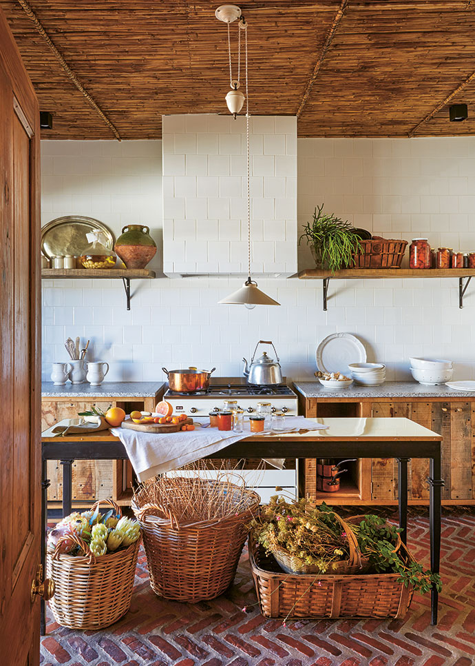 Floor-to-ceiling white tiles make the kitchen appear larger than it is, and klompie-brick flooring and French-oak cabinets by Pierre Cronje add the feel of an old Karoo kitchen.