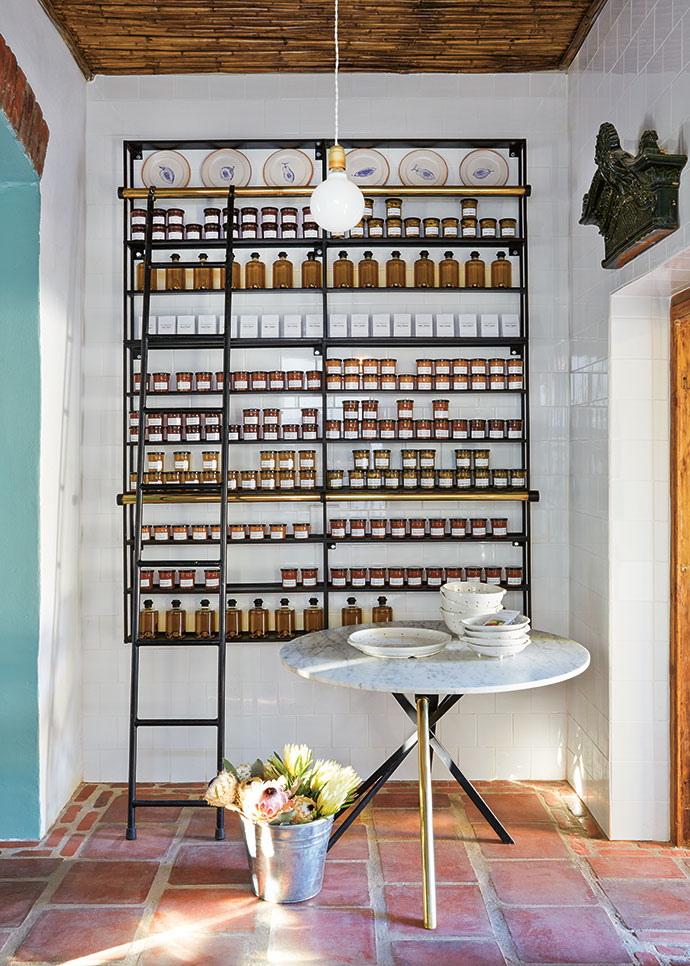 A steel-and-brass shelf in the shop holds an array of jams and preserves made from produce grown in the garden. The table is a bespoke design by Jacques's interiors studio.