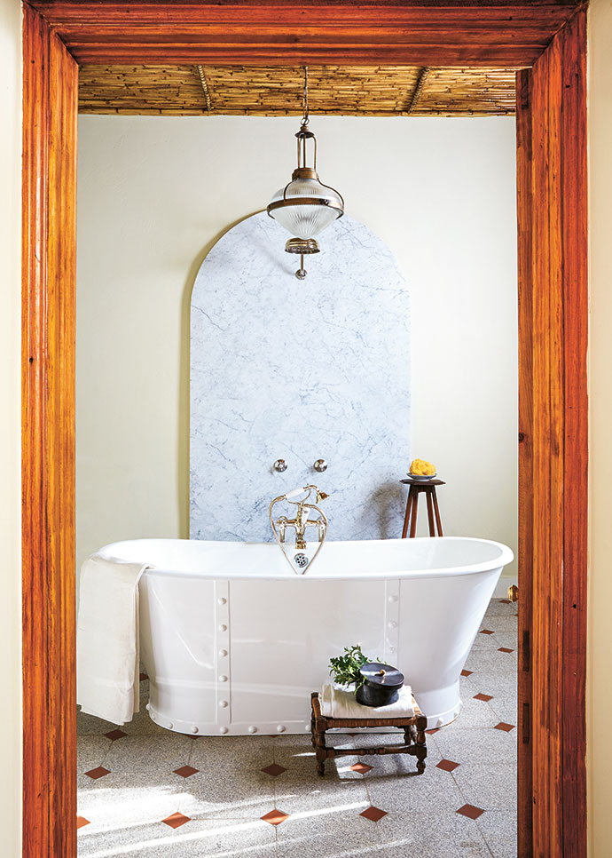 The granite floor, which is cool in summer and warm in winter; the open shower in front of an arched marble slab; and the bespoke cast-iron bath made by Jacques's interiors studio take this bathroom to the next level.