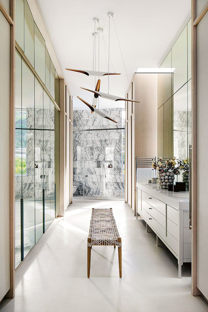 In the airy master bedroom en-suite and dressing area, white screed floors blend with mirrored wardrobes and sanitaryware by ProjiSpec. The teak Spindle bench with its woven-leather riempie seat is from Weylandts.