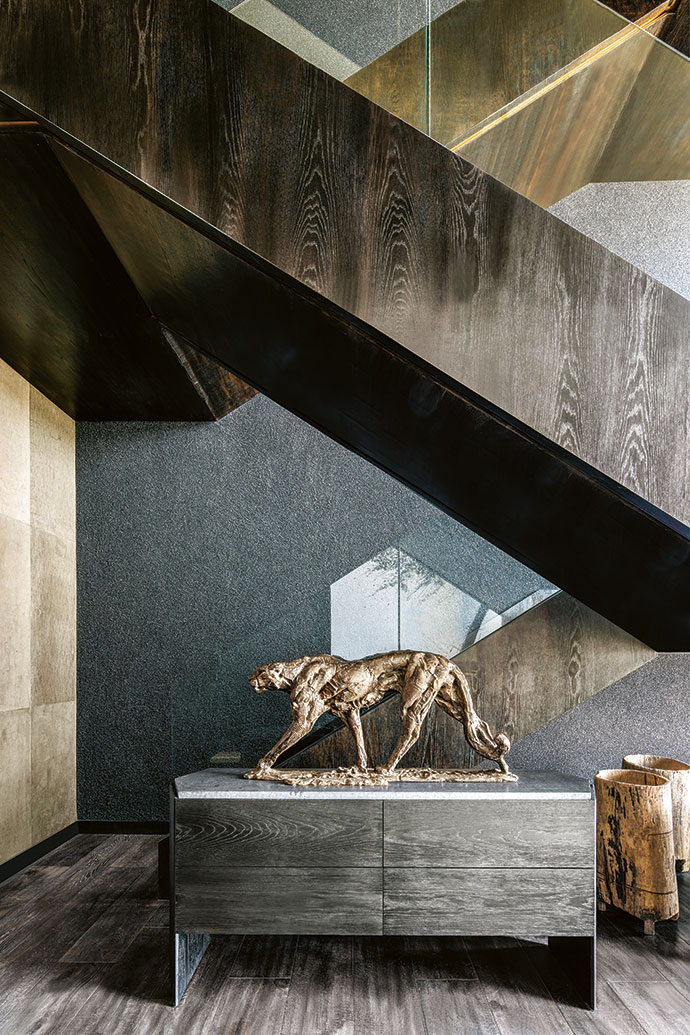 The sculptural staircase is defined by chocolate oak that lightens in hue as it progresses upwards through the house. The textured wall features volcanic sand that lightens into pale white on the upper levels. The cat sculpture is by Dylan Lewis.
