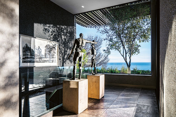 Interlinking statues by Angus Taylor form a focal point on the garden level, where textured stone leads to an outdoor braai area. Nicholas Whitehorn did the landscaping.