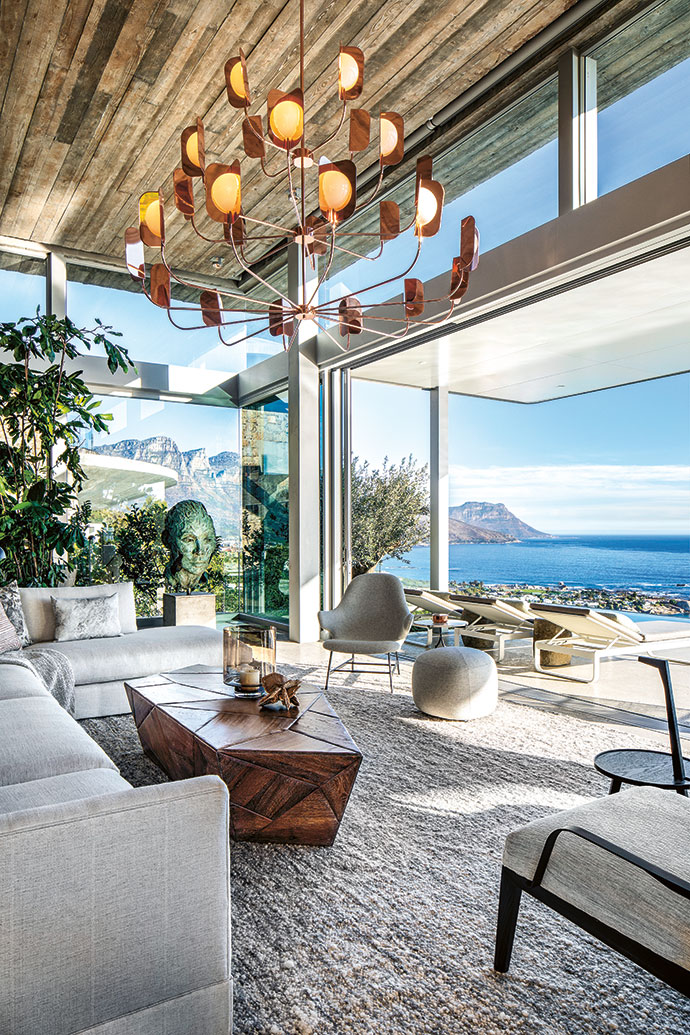 The sea-facing aspect of the main living area features an off-shutter concrete ceiling. Cécile & Boyd custom-made the fumed oak coffee table and lounge suite. The Catch chair was designed by Jaime Hayon for &tradition, the Leaf chandelier is by Lampadari, and the bronze sculpture is by Lionel Smit.