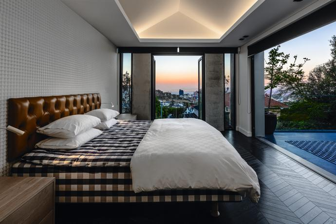 The Hästens bed in the master bedroom had to be delivered to the top floor by crane as it couldn't fit up the spiral staircase. The sculptural wall-covering is Ajanta 06 Sterling by Wemyss Fabrics, sourced locally from Home Fabrics, and the chevron flooring is Oggie.