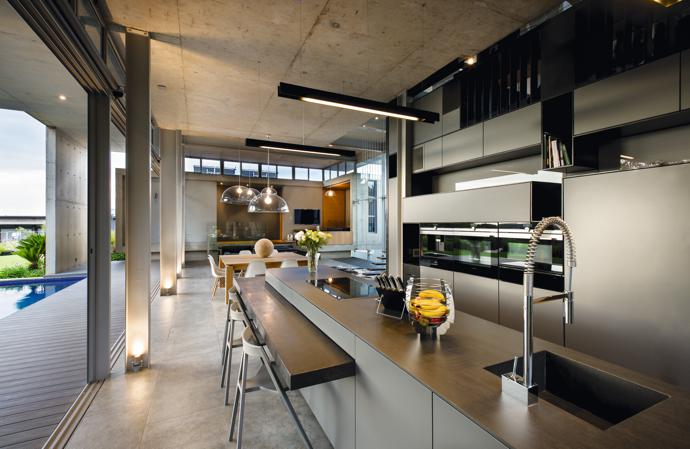 The sleek, industrial look of the kitchen was achieved by combining high-gloss laminated cabinetry with a precision-cut steel framework and Neolith sintered stone countertops. The granite of the breakfast nook was honed to add a sense of warmth to the touch.