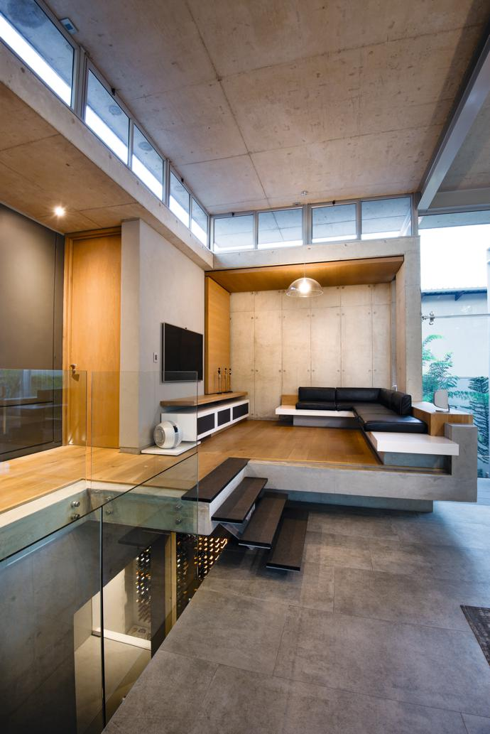 Floating on a plinth of exposed concrete, the bespoke built-in sofa, with integrated consoles, was designed by Kristen Page from Inside Interiors, an affiliate of Earthworld Architects, and manufactured by Nic Gaudard from Swiss Joinery.