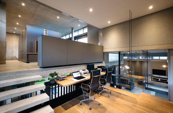 """Adéle's office was designed to allow for privacy while still being """"a part of it all"""". Storage space was incorporated into the structure, with the suspended steel balustrade doubling as shelving space and extra cupboard space in the room divider."""
