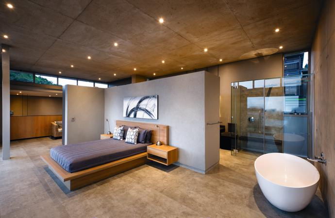 The theme of openness and transparency is continued into the master bedroom, where a low-level screen wall wraps around the bed to create an intimate nook within the spacious open-plan layout of the room.