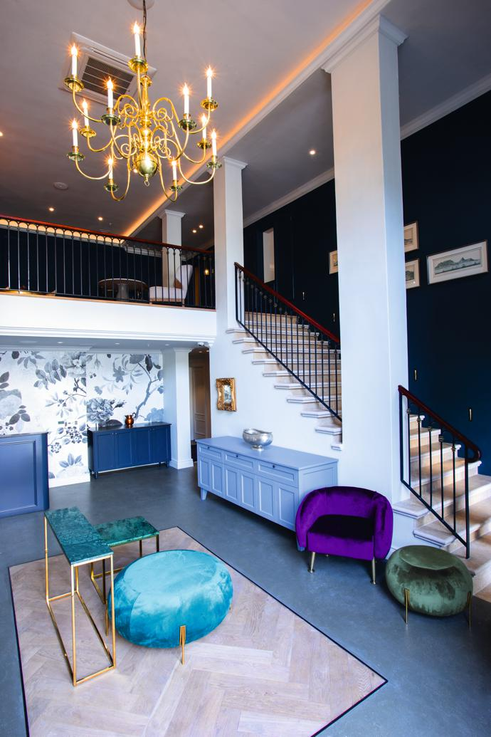 The hotel's double-volume entrance hall with chairs by LEON at CCIXX below a 17th-century Flemish chandelier. The custom cabinets are by MSM Kitchens and the small furniture pieces sourced by SKEP Studio.