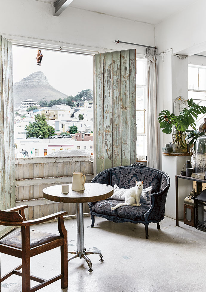 Seen through industrial doors on one side of the loft, Lion's Head soars above the Bo-Kaap's homes, shops and mosques. Francois' cat, Pepe, perches on the black loveseat sourced from Egypt and upholstered in a black T&Co Fabrics damask velvet.