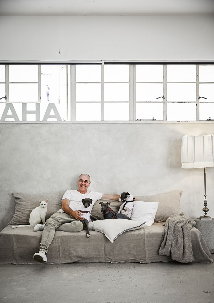 """Francois lounges on the couch with his cat, Pepe, and his three dogs, Ru, Willow and Kio. The couch is covered in vintage French linen bought for """"next to nothing"""" in Marché Saint-Pierre and the lampshade on the right was designed and made by Francois to fit the lamp stand he recently rediscovered in a storeroom."""