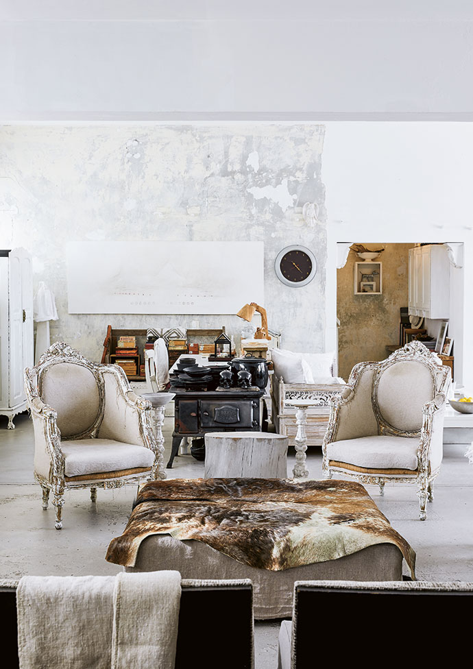 """The main sitting area features a pair of French-style armchairs owner Francois Irvine bought in Egypt and had re-upholstered locally in cream linen. The cast-iron wood-burning stove is a vintage piece he sourced, though it is no longer in use because """"it smokes too much"""". The two white-painted, four-legged wooden stools are from West Africa."""