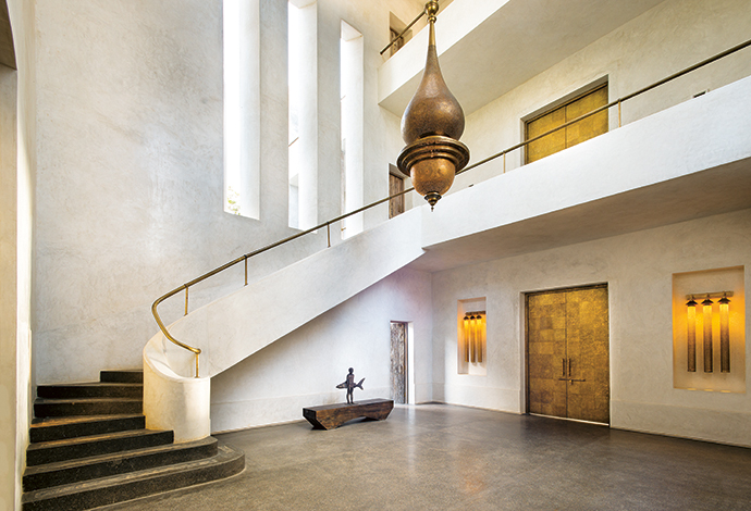 "The monastic arrival foyer features custom-made beaten brass doors as well as bespoke lighting from Marrakesh. The ""Shark Boy"" sculpture is part of the owner's private collection."