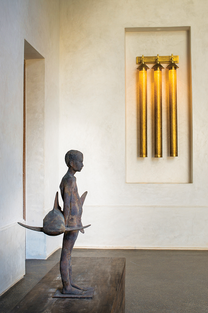 The owners' favourite artwork is highlighted by brass hanging lights from Marrakesh, and the walls have a Lamu plaster finish.