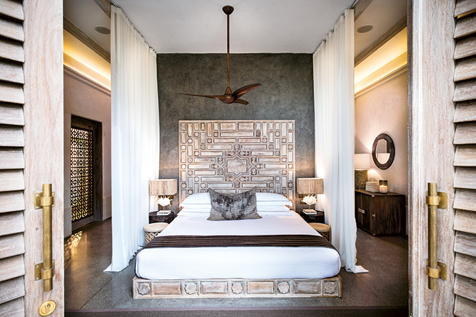 The hand-carved Moorish-inspired bed, framed by soft, romantic mosquito netting, is the hero of this guest suite.