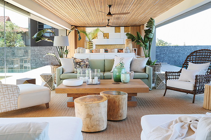 "In the home's covered veranda, a pale green sofa upholstered in St Leger & Viney's Chromatics ""Meadow"", along with an abundance of tropical indoor foliage, echoes the verdant vegetation beyond."